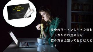 暗い部屋でパソコンを見ながらラーメンを食べる女性